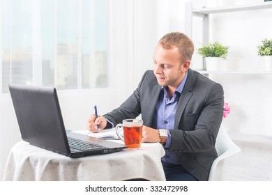 Businessman in office sitting at  table with a laptop writes with concentration.