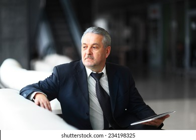 businessman in office with the tablet sits and works