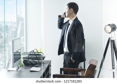 Businessman in office talking with smartphone. Business communication concept.