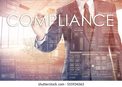 the businessman in the office is writing on the transparent board word associated with the Compliance