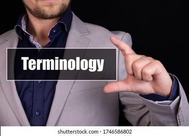 Businessman on a black background holds an icon with the text Terminology