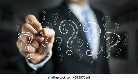 Businessman on blurred background drawing question marks with a pen