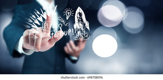 Businessman on blurred background holding hand drawn startup text and red rocket in his hand