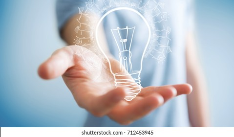 Businessman on blurred background holding renewable eco lightbulb sketch