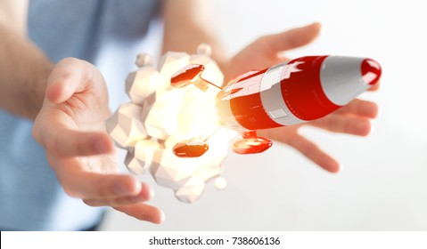 Businessman on blurred background holding red rocket in his hand