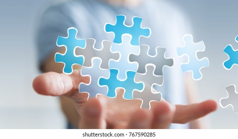 Businessman on blurred background holding hand-drawn puzzle pieces