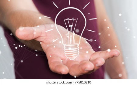 Businessman on blurred background holding a sketch lightbulb