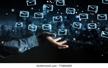 Businessman on blurred background holding and touching floating emails sketch