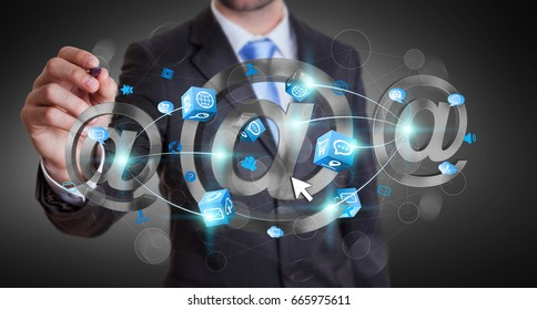 Businessman on blurred background touching 3D rendering email icon with a pen