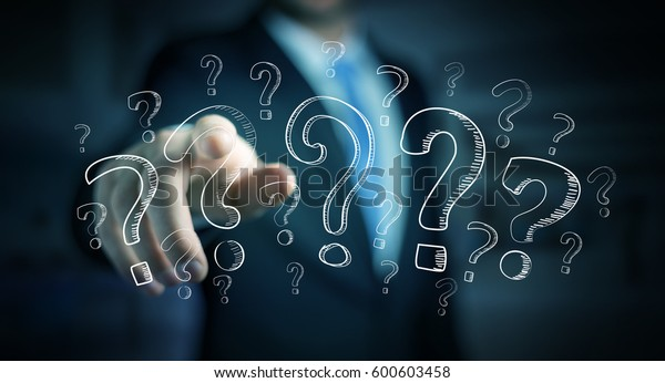 Businessman on blurred background touching hand drawn question marks with his fingers