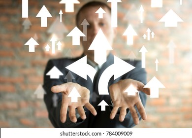 Businessman on blurred background using virtual screen giving and choice arrows icon in his hands. Directions of the company's development.