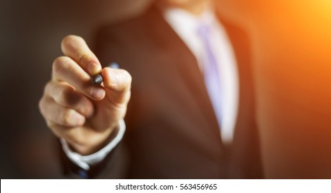 Businessman on blurred background writing with a pen on a digital screen
