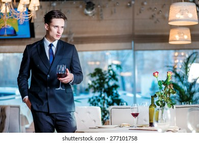 Businessman on a break. Young man businessman in formal wear standing in a restaurant while holding a glass of wine and looking forward
