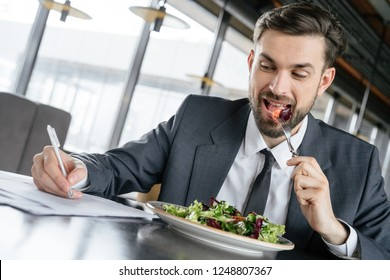 Businessman on business lunch at restaurant sitting at table eating fresh vegetable salad signing contract smiling joyful