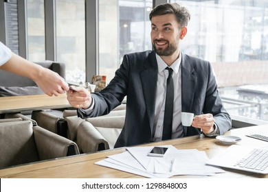 Businessman on business lunch at restaurant sitting at table giving credit card to waitress paying for coffee smiling happy