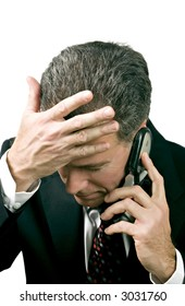 Businessman on a cell phone reacting in a distressed manner to what is being said during a phone conversation.