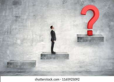 Businessman on concrete ladder looking at question mark. Confusion and solution concept.