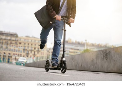 Businessman on daily commute riding micro scooter