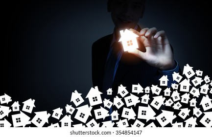 Businessman on dark background taking house icon with fingers