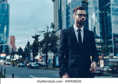 Businessman on the go. Night time image of confident young and handsome man in full suit walking along the street with cityscape in the background