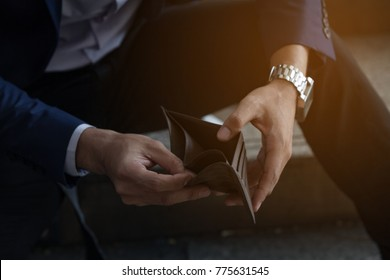 businessman on have money unemployed and bankrupt looks into his empty wallet.  Stress crisis, unemployed businessmen are waiting for new jobs, recession situation and hopelessness crisis concept.