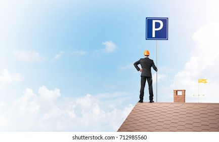 Businessman on house top holding car parking board and viewing city. Mixed media