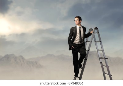 Businessman on a ladder and mountains in the background