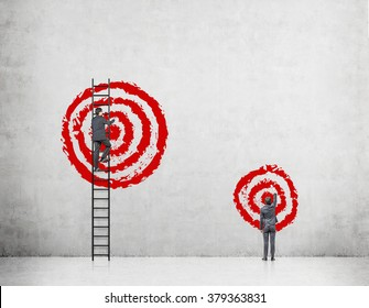A businessman on a ledder painting a big red target, the other one standing on the floor painting a smaller target. Concrete background. Back view. Concept of goal-setting.