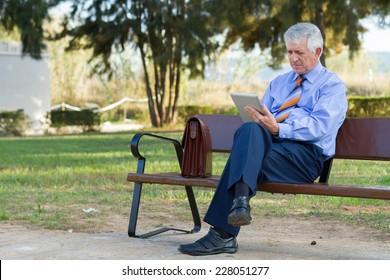 Businessman on park bench using tablet