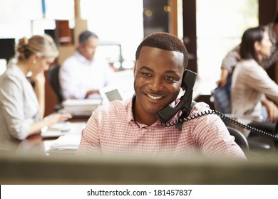 Businessman On Phone At Desk With Meeting In Background