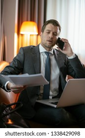 Businessman on the phone at a hotel room. Executive manager talking on the phone.