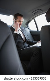 Businessman on the phone reading the newspaper in his car