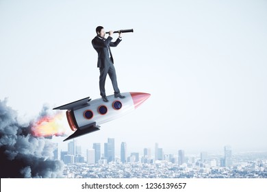 Businessman on rocket looking into the distance with telescope on light city background. Startup and entrepreneurship concept.