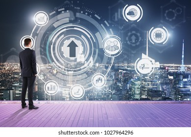 Businessman on rooftop looking at abstract business hologram. Night city background. Innovation and finance concept. Double exposure