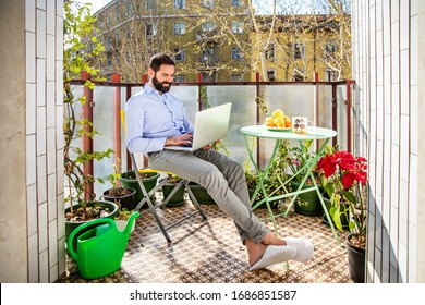 Businessman on smart working using laptop sitting on the balcony at his home
