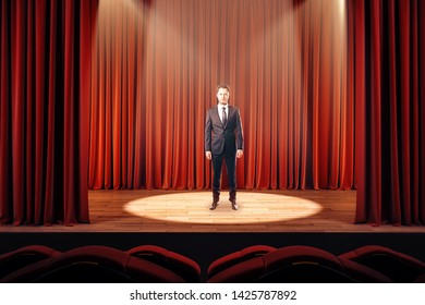 Businessman on stage with red curtains. Leadership concept.