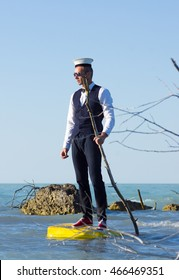 Businessman on a suitcase floating in the sea