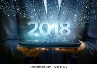 Businessman on tablet shows the numbers 2018. The concept of a new year.