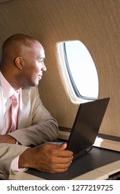 Businessman on trip with laptop on airplane during flight
