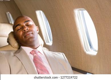 Businessman on trip sleeping in seat on airplane during flight