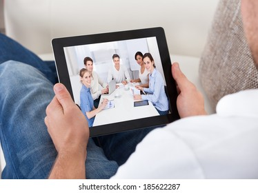Businessman on a video call chatting to colleagues in a meeting visible on the screen of his tablet