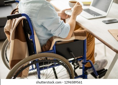 Businessman on wheelchair sitting by desk and having tea or coffee in front of laptop
