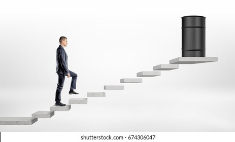 A businessman on white background walking up a concrete block stairs where a black oil barrel stands on the top. Oil and gas industry. Procurement business. Commodities trading.