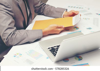 Businessman open brown envelope for evaluating business report, examining report papers on table in desk office.