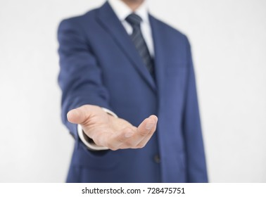 Businessman with open hand. Holding, giving, showing concept.