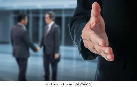 Businessman with an open hand ready for handshake to seal a deal standing in office