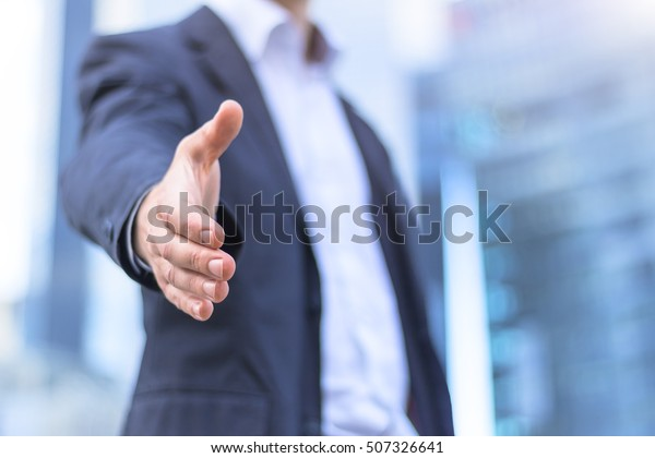 Businessman with an open hand ready for handshake - concept about agreement, partnership and win-win situation