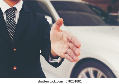 Businessman with an open hand ready to sale car deal