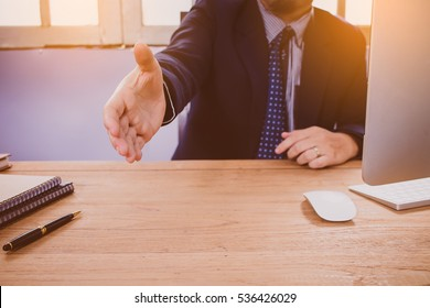 Businessman with an open hand ready to seal a deal in office.