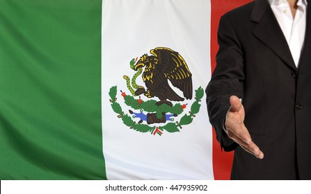Businessman with an open hand waiting for a handshake concept for business with the Mexico flag in the background